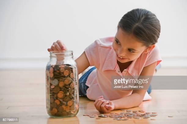 Hispanic girl dropping coins in jar
