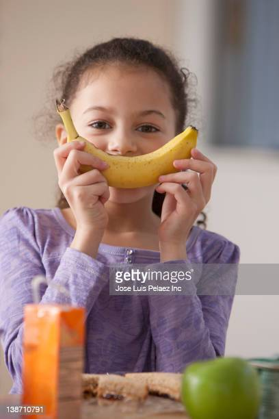 hispanic girl eating banana for lunch at school - kid girl eating apple stock photos and pictures