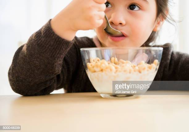 Hispanic girl eating bowl of cereal