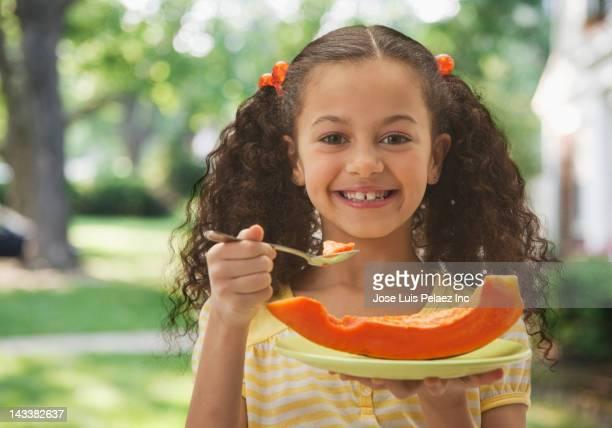 hispanic girl eating cantaloupe - 8 9 años fotografías e imágenes de stock