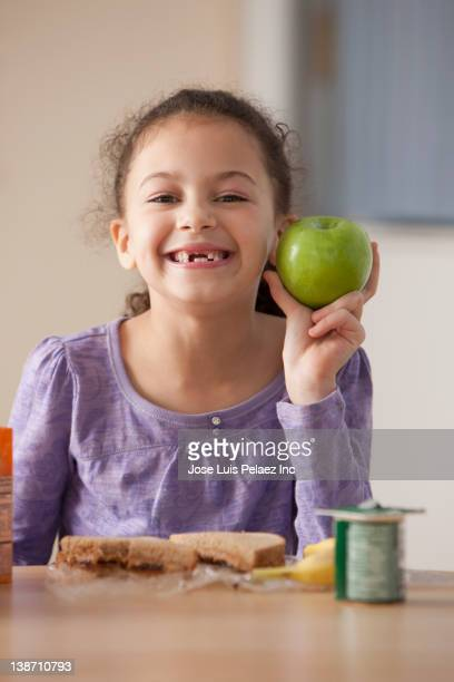 hispanic girl eating lunch at school - kid girl eating apple stock photos and pictures