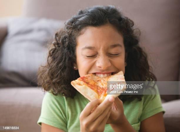 Hispanic girl eating pizza