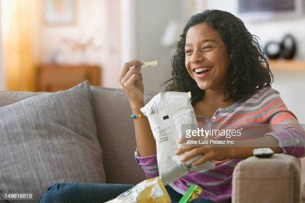 Hispanic girl eating potato chips on sofa