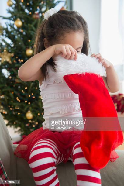 Hispanic girl examining Christmas stocking