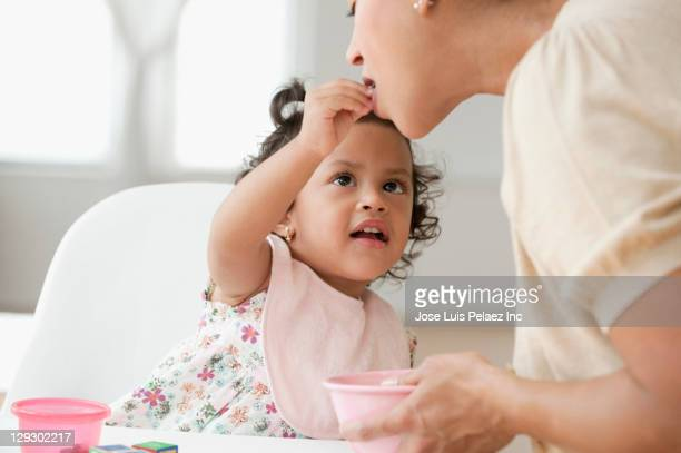 Hispanic girl feeding mother