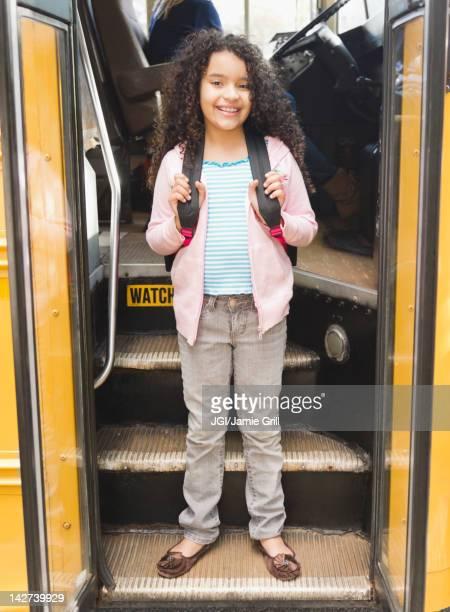 Hispanic girl getting onto school bus