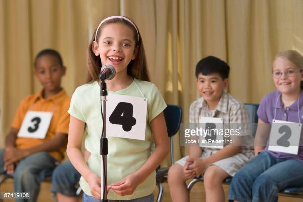Hispanic girl giving answer in spelling bee