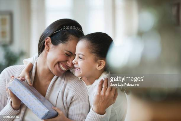 hispanic girl giving mother birthday gift - gift stock pictures, royalty-free photos & images