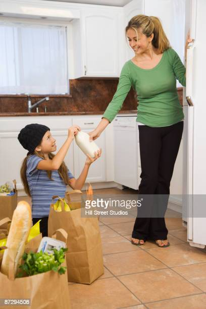 Hispanic girl helping mother put away groceries