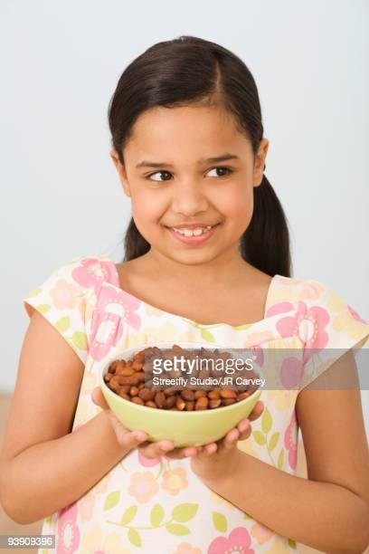 Hispanic girl holding bowl of almonds