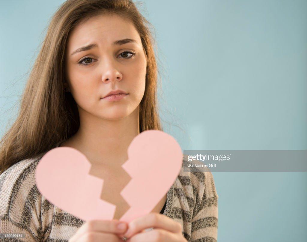 Hispanic girl holding broken heart shape : Stock Photo