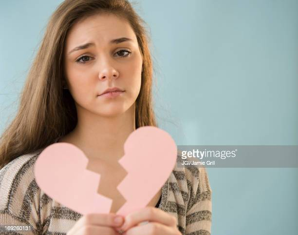 Hispanic girl holding broken heart shape