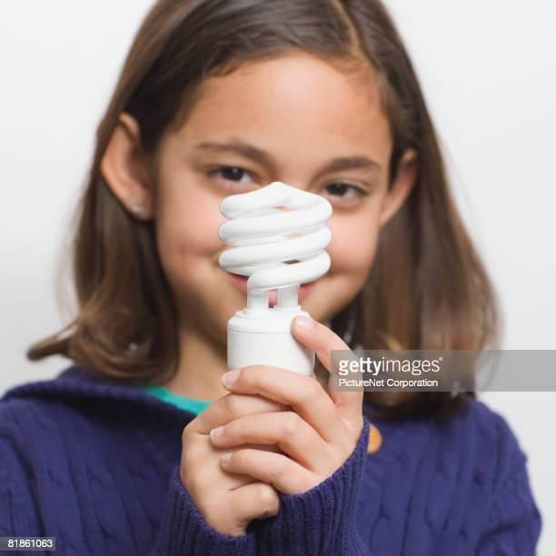 Hispanic girl holding energy efficient light bulb