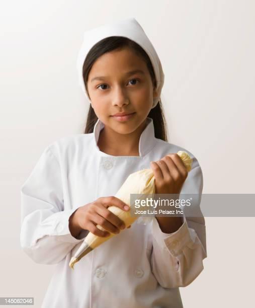 Hispanic girl holding frosting bag