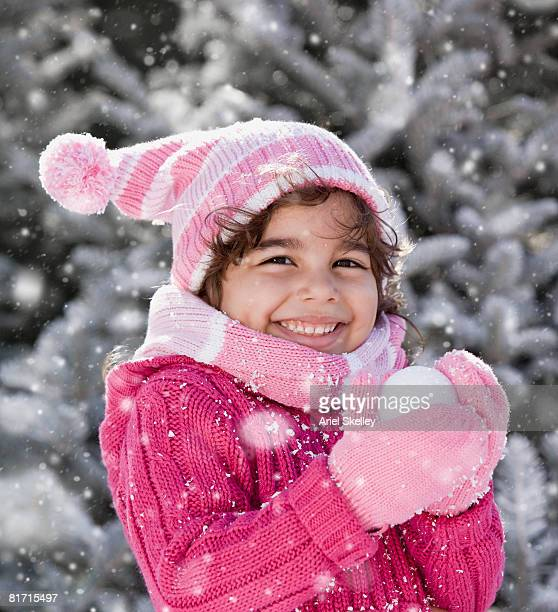 Hispanic girl holding snowball