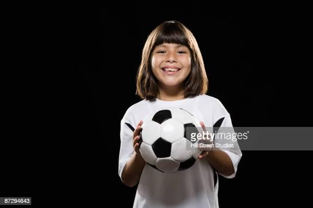 Hispanic girl holding soccer ball