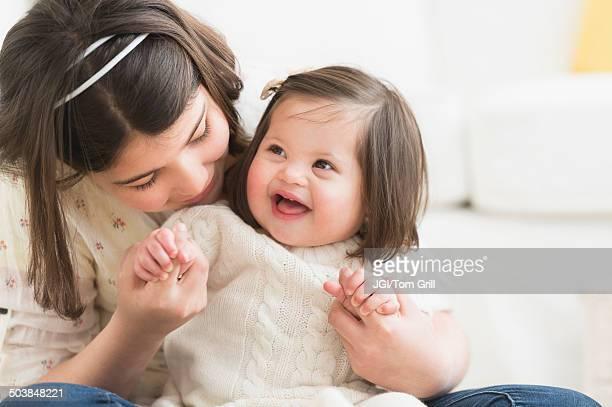 Hispanic girl holding toddler sister in living room