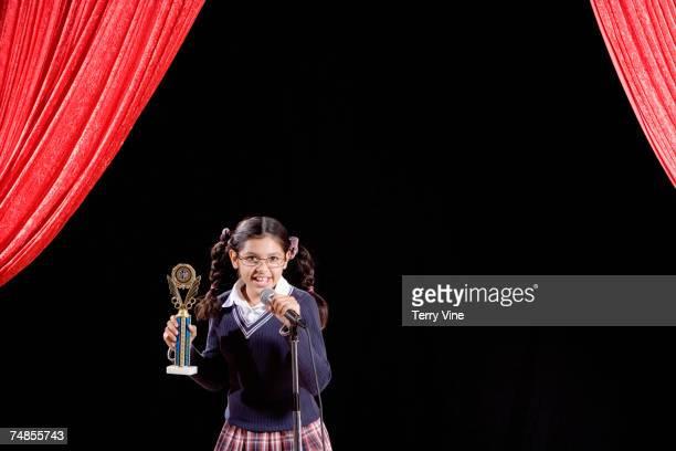 Hispanic girl holding trophy on stage