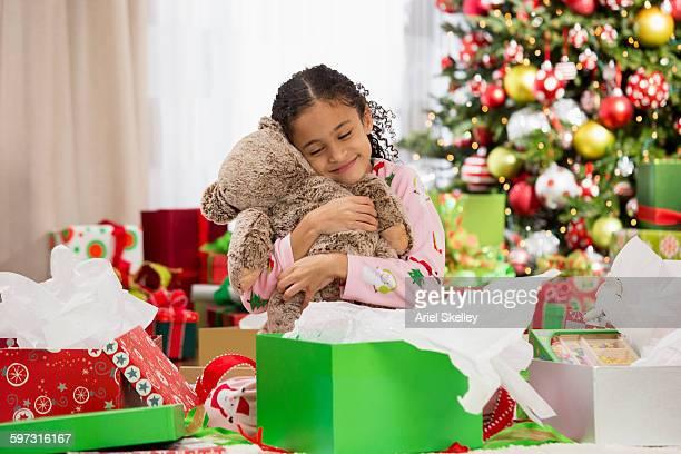 Hispanic girl hugging teddy bear Christmas gift
