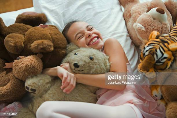 Hispanic girl hugging teddy bear in bed