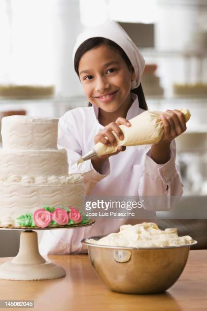 hispanic girl icing wedding cake - decorating a cake stock pictures, royalty-free photos & images