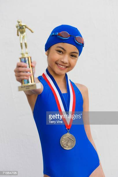 Hispanic girl in bathing suit with metal and trophy