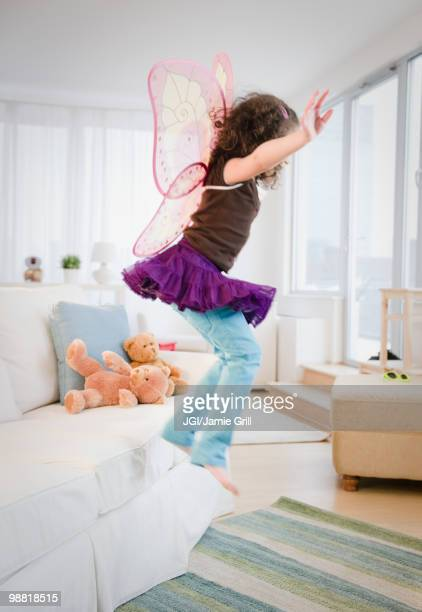Hispanic girl in fairy wings jumping off couch