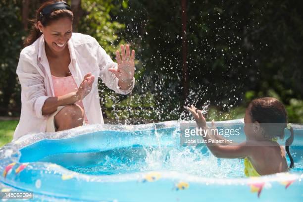 Hispanic girl in kiddie pool splashing mother