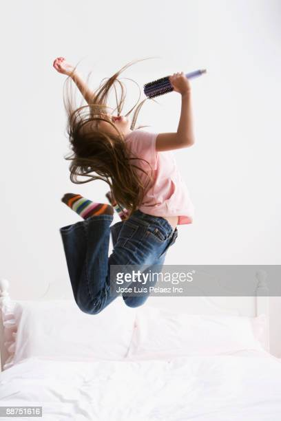 Hispanic girl jumping and singing into hairbrush