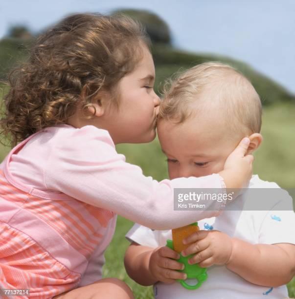 Hispanic girl kissing baby
