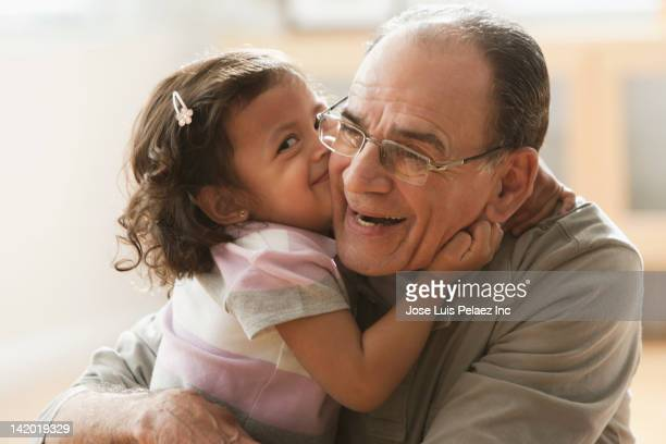 Hispanic girl kissing grandfather
