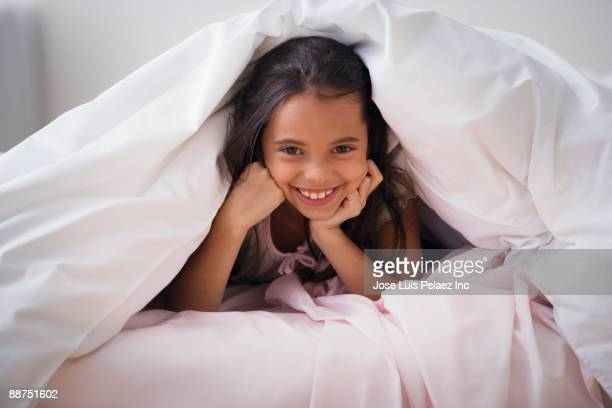 Hispanic girl laying underneath covers in bed