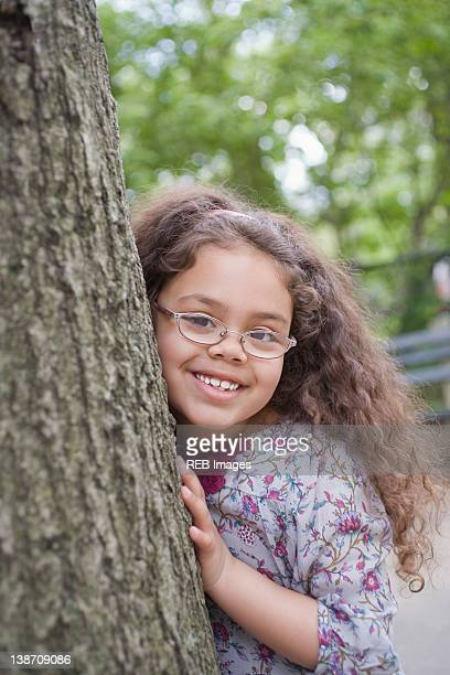 Hispanic girl leaning on tree trunk