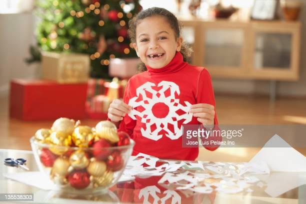 Hispanic girl making Christmas paper snowflake