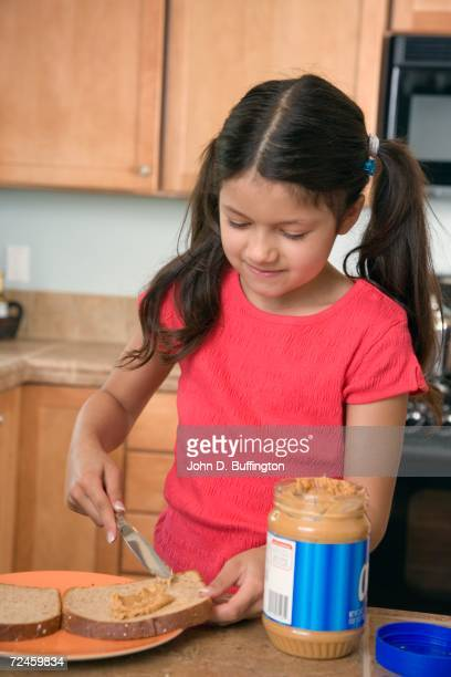 Hispanic girl making peanut butter and jelly sandwich