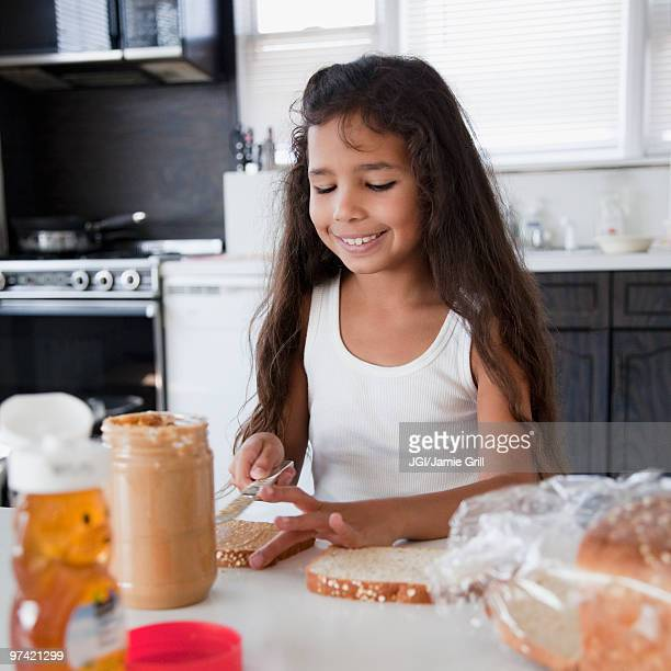 Hispanic girl making peanut butter sandwich