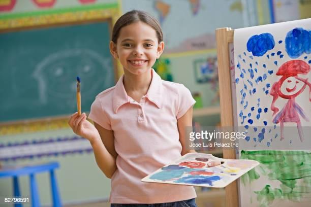hispanic girl painting in classroom - 6 7 anni foto e immagini stock