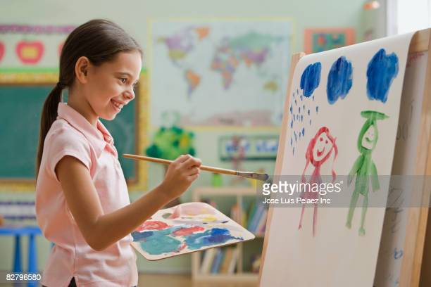 Hispanic girl painting picture in classroom