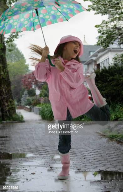 Hispanic girl playing in rain
