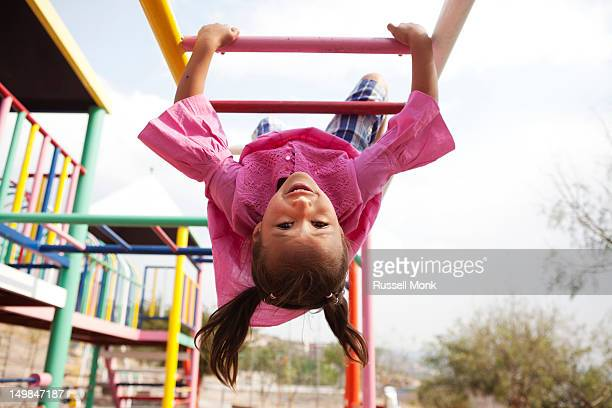Hispanic girl playing in the monkey bars.