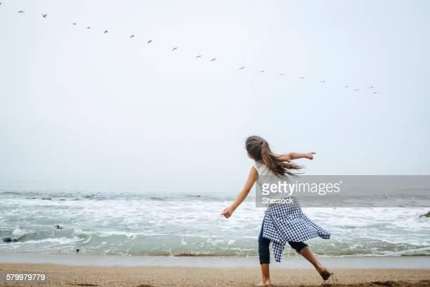 Hispanic girl playing on beach