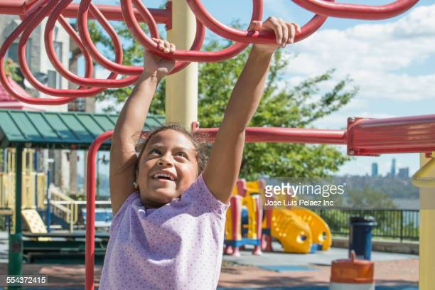 Hispanic girl playing on monkey bars at playground