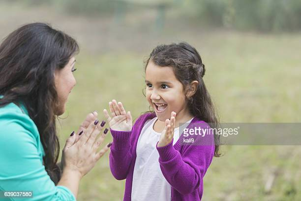 Hispanic girl playing patty cake with mother