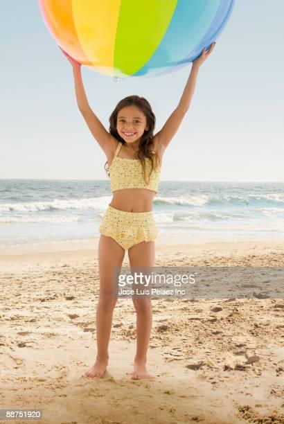 Hispanic girl playing with ball at beach