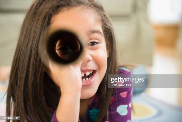 Hispanic girl playing with cardboard tube
