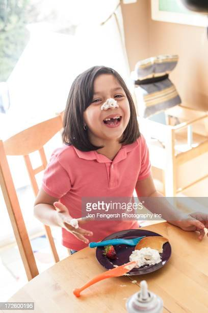 Hispanic girl playing with food at table