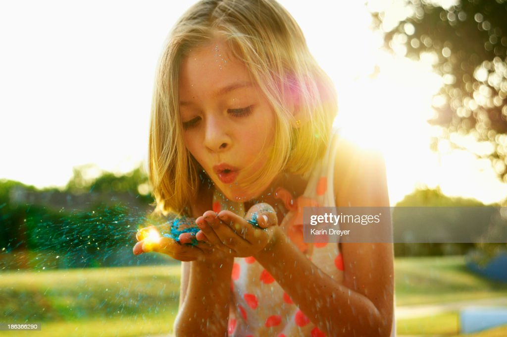 Hispanic girl playing with glitter outdoors : Stock Photo