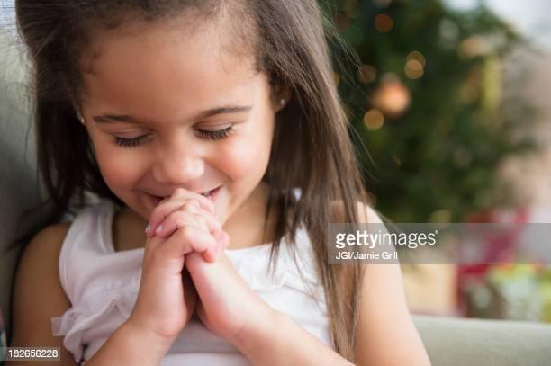Hispanic girl praying on sofa