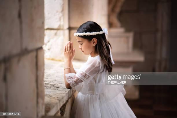 hispanic girl praying - communion stock pictures, royalty-free photos & images