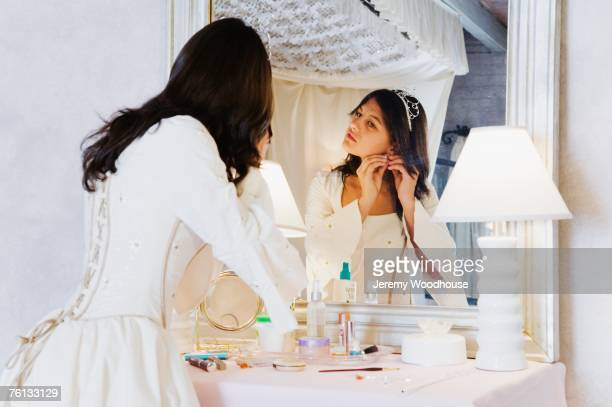hispanic girl putting on earring in quinceanera dress - quinceanera stock pictures, royalty-free photos & images